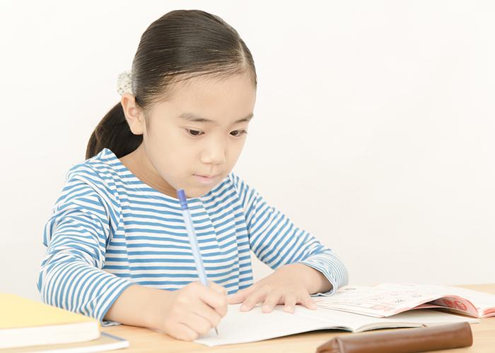一生懸命字を書く少女