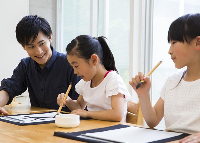 並んで楽しそうに習字を習う女子